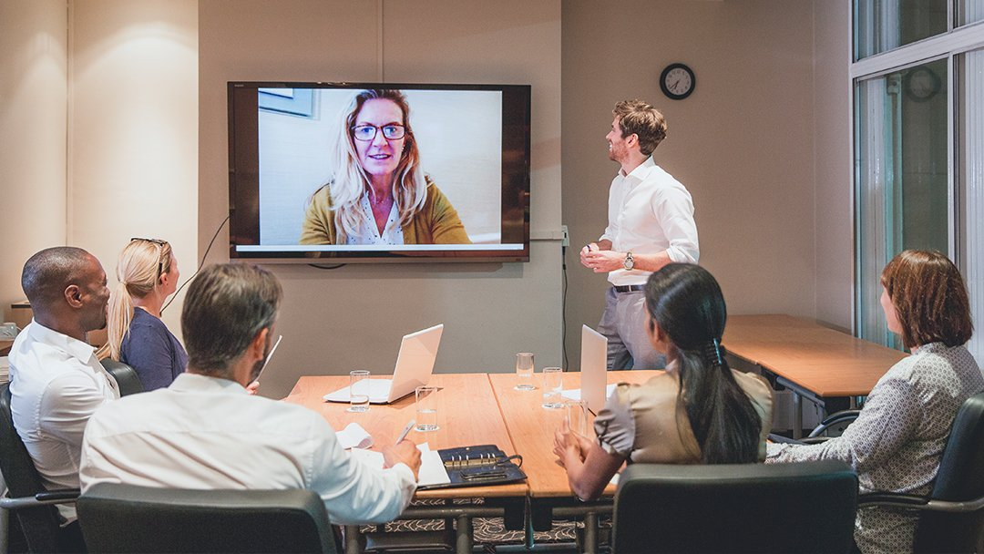 Woman on screen leading virtual meeting with distributed team