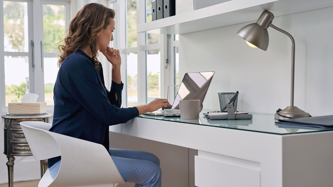Woman working remotely at a laptop in her home office